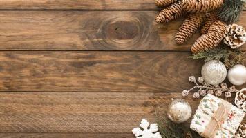 Caja de regalo con adornos brillantes y piñas sobre fondo de madera foto