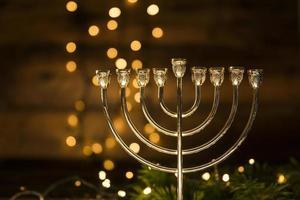 Golden menorah in dark room with golden bokeh lights photo