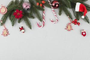 ramas de abeto verde con bastones de caramelo y juguetes pequeños foto