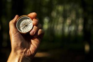 Hand holds compass with blurred background
