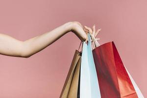 mano con coloridas bolsas de la compra sobre fondo rosa foto