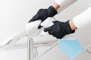 manos con guantes desinfectando pasamanos foto