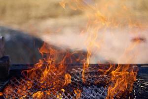Fuego en una parrilla vintage oxidada al aire libre con fondo borroso foto