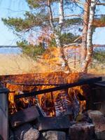 Fuego en una parrilla vintage oxidada al aire libre en la playa del mar foto
