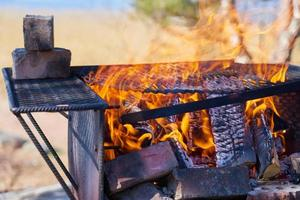 Fire in a rusty vintage grill outdoor on the beach of the sea photo