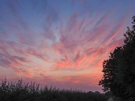 hermosas nubes rosadas y púrpuras en el cielo al atardecer foto