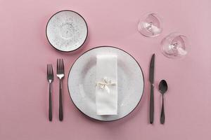 White table setting on pink background photo