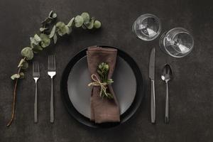 Dark grey and brown table setting with eucalyptus photo