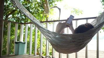 Asian Woman Using Smartphone in a Hammock
