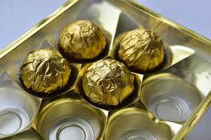 Chocolate candies in a box in a gold wrapper photo