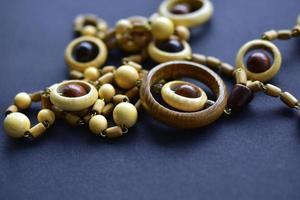 Wooden beautiful round beads on black background photo