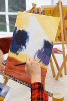 Primer plano de una artista femenina pintando a mano un cuadro en una paleta en el taller foto