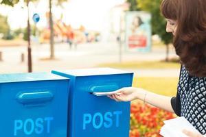 mujer pone cartas en el buzón foto