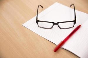 Composición empresarial con gafas y bolígrafo para portátil. foto