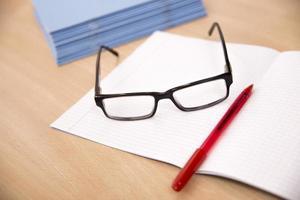 composición empresarial con gafas y bolígrafo portátil foto