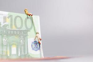 Miniature people, climber climbs on a Euro banknote, business concept. photo