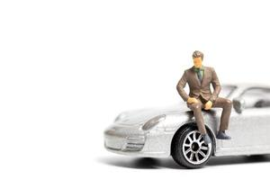 Miniature people, businessman sitting on a car and copy space for text photo