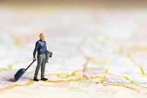 Empresario en miniatura de pie en el mapa, concepto de viaje foto