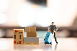 Miniature people, postman officers on duty preparing to send a box to the consumer. Delivery service for e-commerce concept photo