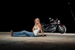 Sexy blonde sitting near her motorcycle photo