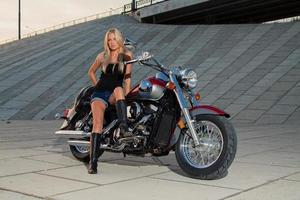 Sexy blonde sitting on her motorcycle photo