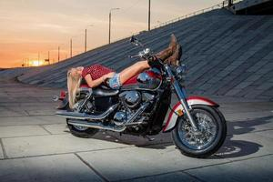 Sexy blonde lying on her motorcycle photo