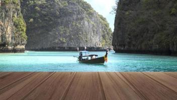 Mesa de madera en la vista superior del hermoso mar y barco de madera con montañas en resort tropical durante un día de verano foto