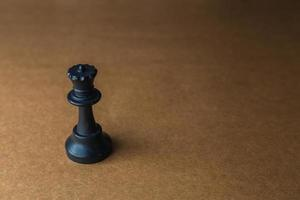 pieza de ajedrez reina sobre un fondo marrón foto
