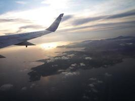 Sunrise and airplane wing view from illuminator. photo