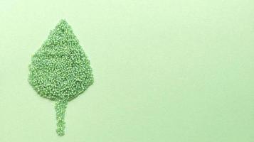 Hoja de perlas verdes hechas a mano sobre fondo de textura pastel. endecha plana con espacio de copia. foto de stock.