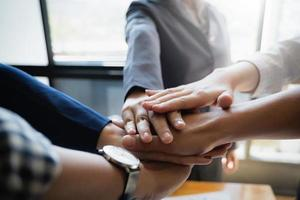 Group of businesspeople putting their hands working together in an office. Group support, teamwork agreement concept. photo