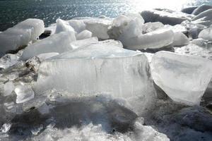 bloques de hielo en una orilla junto a un cuerpo de agua foto