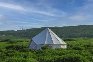 White tent in a field with cloudy blue sky photo