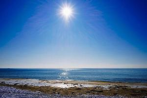 Seascape of a shoreline and a body of water with bright sun and a clear blue sky photo