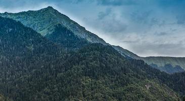 paisaje con montañas y bosques con un cielo azul nublado en abjasia foto