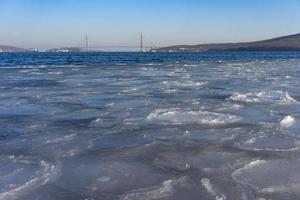 Cuerpo de agua cubierto de hielo y el puente russky en el fondo en Vladivostok, Rusia foto