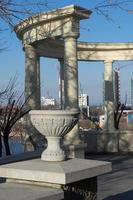 Jarrón de piedra decorativa junto a una columnata con un paisaje urbano en el fondo en Vladivostok, Rusia foto