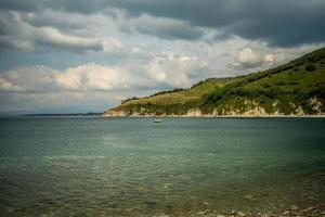 Seascape of a rocky shoreline at a body of water with mountains and cloudy blue sky in Nakhodka, Russia photo
