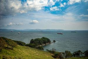 Seascape of a shoreline with mountains and cloudy blue sky at Nakhodka Bay in Nakhodka, Russia photo