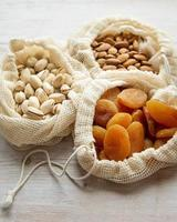 Eco bags with pistachios, almonds and dried apricots photo