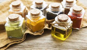 frascos con hierbas secas, especias sobre la mesa foto