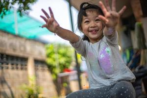 Happy Asian little girl playing and showing dirty hands outdoors. photo