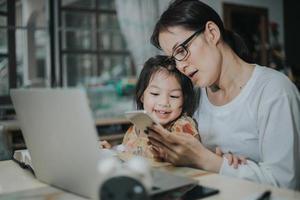 mujer asiática enseñando a su hija con computadora portátil y teléfono inteligente, estudiando el concepto en línea. foto