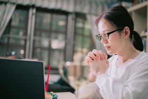 Cerca de las manos de la mujer rezando con el portátil en casa. foto