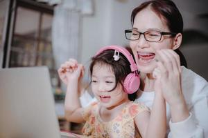 A mother is putting headphones on her daughter to help her study online. photo