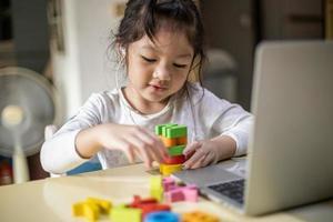 niña asiática que aprende alfabetos en línea, niña feliz que aprende en línea con una computadora portátil en casa. nuevo normal. coronavirus covid-19. distanciamiento social. quedarse en casa foto