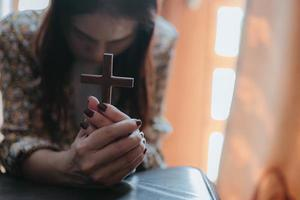A woman is praying, she has a cross in her hands with her head bowed down. photo