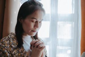 A woman is praying with her eyes closed.