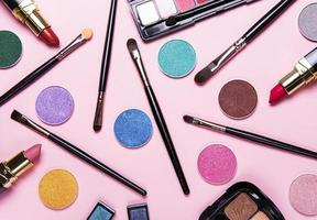 Eyeshadow and brushes on a pink background
