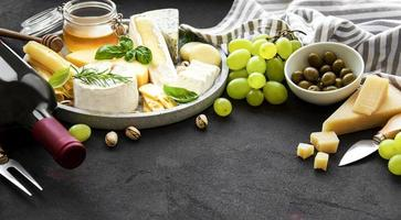queso, uvas, vino y snacks foto